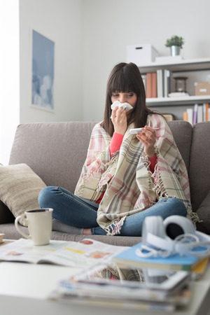 Sick woman with cold and flu, she is resting on the sofa at home and measuring body temperature with a thermometer