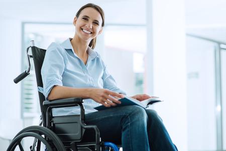 Glimlachende jonge vrouw die in rolstoel camera bekijkt