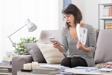 Mujer sorprendida en casa comprobando costosas facturas de la electricidad y el hogar, concepto de finanzas en el hogar