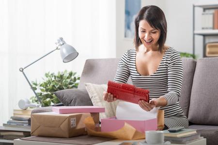 Happy vrouw unboxing een pakket met daarin een mode-tas, online winkelen, levering en klanttevredenheid begrip Stockfoto