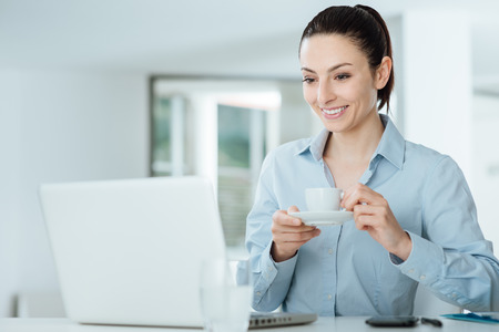 Smiling woman watching a video on her laptop during a coffee break photo