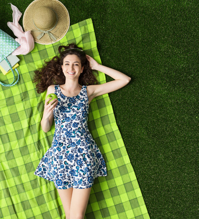 woman lying: Young smiling woman relaxing at the park, she is eating an apple and lying on the grass Stock Photo