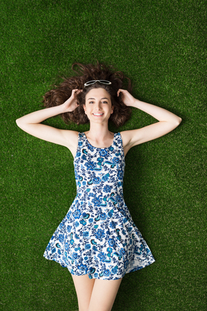 grass beautiful: Happy young woman relaxing on the grass and lying down with hands behind head, relaxation and nature concept