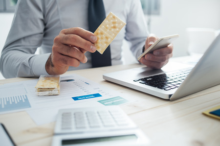 unrecognizable person: Businessman having a snack at desk holding a cracker and a smart phone, hands close up, unrecognizable person