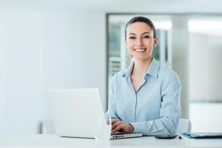 Glimlachend jonge zakenvrouw werken bij bureau en het typen op een laptop, is ze op zoek naar camera