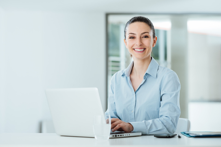 Smiling young businesswoman working at office desk and typing on a laptop, she is looking at camera photo