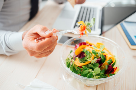 unrecognizable person: Businessman having a lunch break at desk, he is eating fresh salad, unrecognizable person