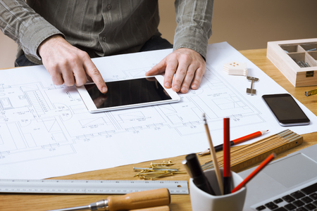 quantity surveyor: Professional architect and construction engineer working at office desk hands close-up, he is using a touch screen tablet