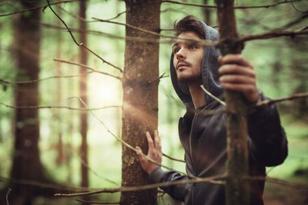 young male: Hooded guy in the woods exploring nature, individuality and freedom concept
