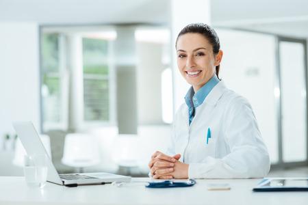 女性医師のオフィスの机で働いて、カメラ、背景にオフィスのインテリアで笑顔