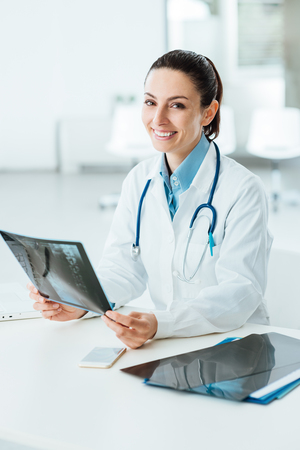 Smiling confident female doctor sitting at office desk and examining a patients x-ray, she is looking at camera Stock Photo