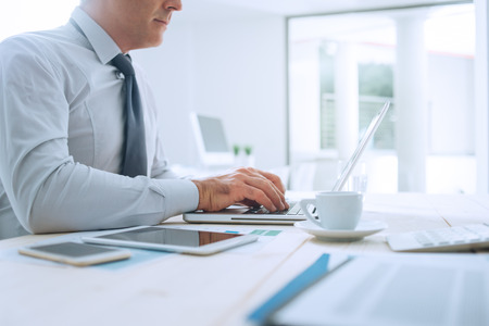 unrecognizable person: Professional businessman working at office desk and typing on a laptop, unrecognizable person