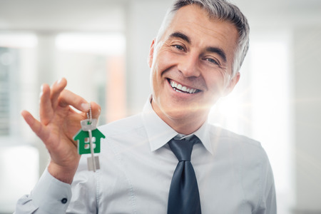 Confident real estate agent holding your new house keys and smiling at camera Stock Photo
