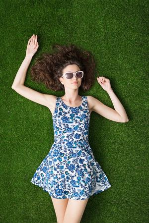 젊은 매력적인 여자 잔디에 편안 하 고 선글라스, 여름 및 청소년 개념을 입고