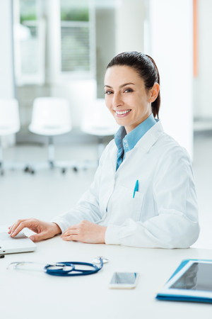 Female doctor working at office desk and smiling at camera, she is using a laptop photo