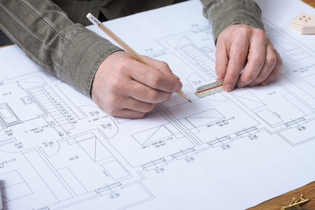 Professional architect and construction engineer working at office desk hands close-up, he is drawing on a building project with a pencil and a ruler Stock Photo