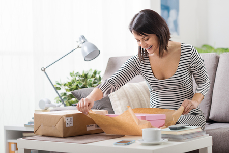 Happy excited woman at home, she has received a postal parcel and she is unboxing her gift, delivery and online shopping concept