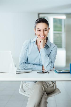 아름다운 자신감을 여성 관리자 사무실 책상에 앉아 턱에 손으로 미소를 카메라 배경에 실내 인테리어 스톡 콘텐츠
