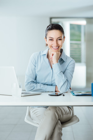 Beautiful confident female manager sitting at office desk and smiling at camera with hand on chin, room interior on background photo