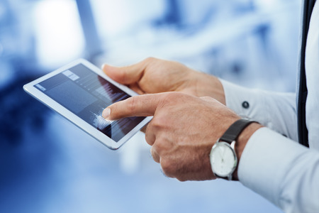 Professional businessman using a digital touch screen tablet, hands close up, unrecognizable person