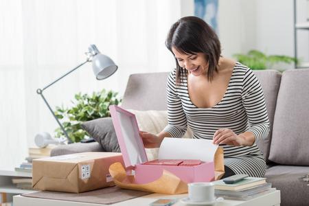 Gelukkig opgewonden vrouw thuis, heeft ze een postpakket ontvangen en ze is unboxing haar gave, levering en online shopping concept Stockfoto