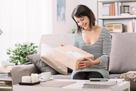 ソファの上で若い女性の笑みを浮かべて、彼女を受けた郵便小包、オンライン ショッピングと配信の概念