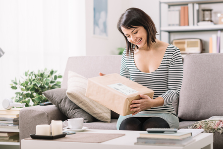 Smiling young woman at home on the couch, she has received a postal parcel, online shopping and delivery concept Stock fotó