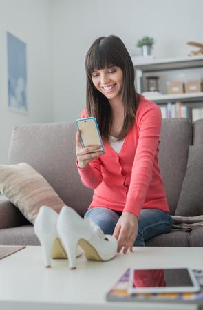 Joven mujer sonriente tomar una foto de sus zapatos con un teléfono inteligente, que va a vender en una tienda en línea
