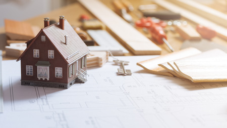 Construction and home renovation concept, model house, work tools, house keys and draft project on a desktop