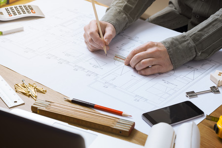 Professional architect and construction engineer working at office desk hands close-up, he is drawing on a building project with a pencil and a ruler Foto de archivo