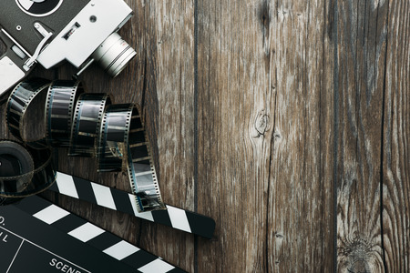 film director: Vintage film camera, filmstrip and clapper board on a wooden desktop, cinema and filmmaking concept Stock Photo
