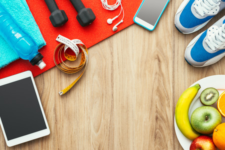 Sport-und Workout-Ausrüstung, digitale Tablette und Obst auf einem Holztisch, Training und gesunde Lebensweise Konzept, flache Lage Standard-Bild