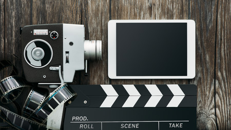 Vintage film camera, tablet, clapper and filmstrip on a wooden table: cinema and entertainment concept