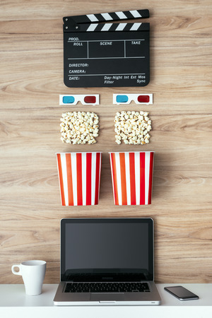 vod: Laptop, popcorn, 3D glasses and clapboard on a wooden surface, cinema and entertainment concept Stock Photo