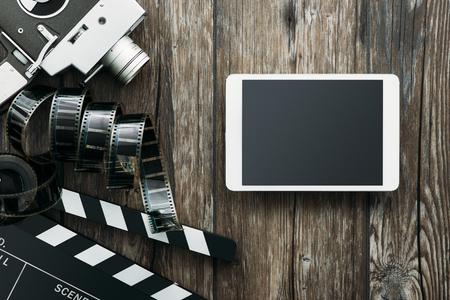 Appareil photo argentique, tablette, clapet et pellicule sur une table en bois: concept cinéma et divertissement Banque d'images - 67097475