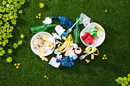residuos organicos: Montón de basura mixta deja en el césped después de un día de campo, cuidado del medio ambiente y el concepto de residuos