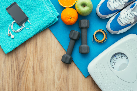 physical activity: Sports and workout equipment on a wooden floor with healthy snacks, weight loss and physical activity concept