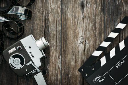 film shooting: Vintage film camera, filmstrip and clapper board on a wooden desktop, cinema and filmmaking concept Stock Photo