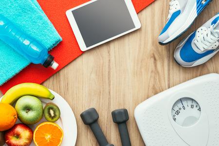 Sport- und Trainingsausrüstung, digitale Tablette und Frucht auf einem Holztisch, einem Training und einem gesunden Lebensstilkonzept, flache Lage