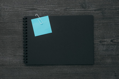 blank note: Blank dark notebook with blue memo note, planning and reminders concept Stock Photo