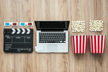 vod: Laptop, clapper board, popcorn and 3D glasses: cinema streaming and movie series online concept Stock Photo