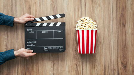 Film director holding a clapper board and popcorn, filmmaking and cinema concept Фото со стока
