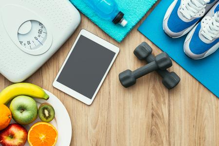 Sport- en fitnessapparatuur, digitale tablet en fruit op een houten tafel, training en een gezonde levensstijl concept, plat Stockfoto