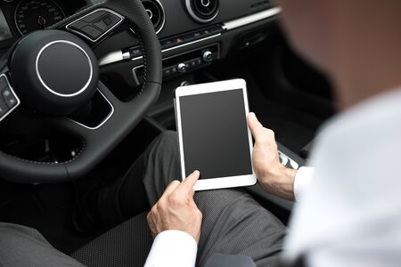 expensive car: Businessman driving his expensive car and connecting with a digital tablet, he is using mobile apps and GPS, car interior