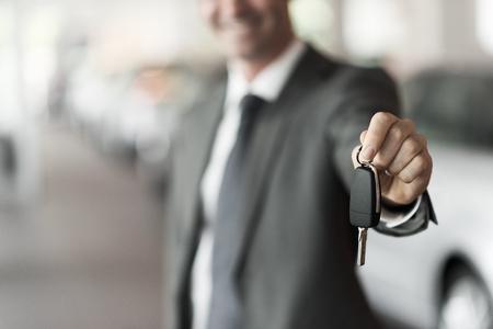 Glimlachende autoverkoper die uw nieuw autosleutels, het handel drijven en verkoopconcept overhandigen Stockfoto