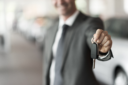 Smiling car salesman handing over your new car keys, dealership and sales concept Stock Photo - 65343879