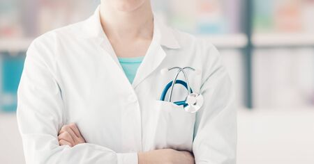 unrecognizable person: Female doctor posing with arms crossed, stethoscope on foreground, unrecognizable person, healthcare concept Stock Photo