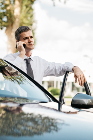 travelling salesman: Confident businessman having a phone call with his smartphone and leaning on the car door