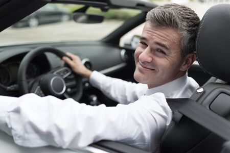 new car: Successful confident businessman driving to work with his brand new expensive car, he is smiling at camera