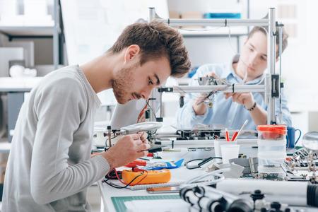 Estudiantes de ingeniería que trabajan en el laboratorio, un estudiante está usando un voltaje y probador de corriente, otro estudiante en el fondo está usando una impresora 3D